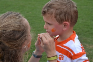 Getting his first ever tiger paw painted on his face.