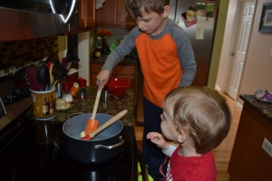 Allowing his little brother to help melt the marshmallows.